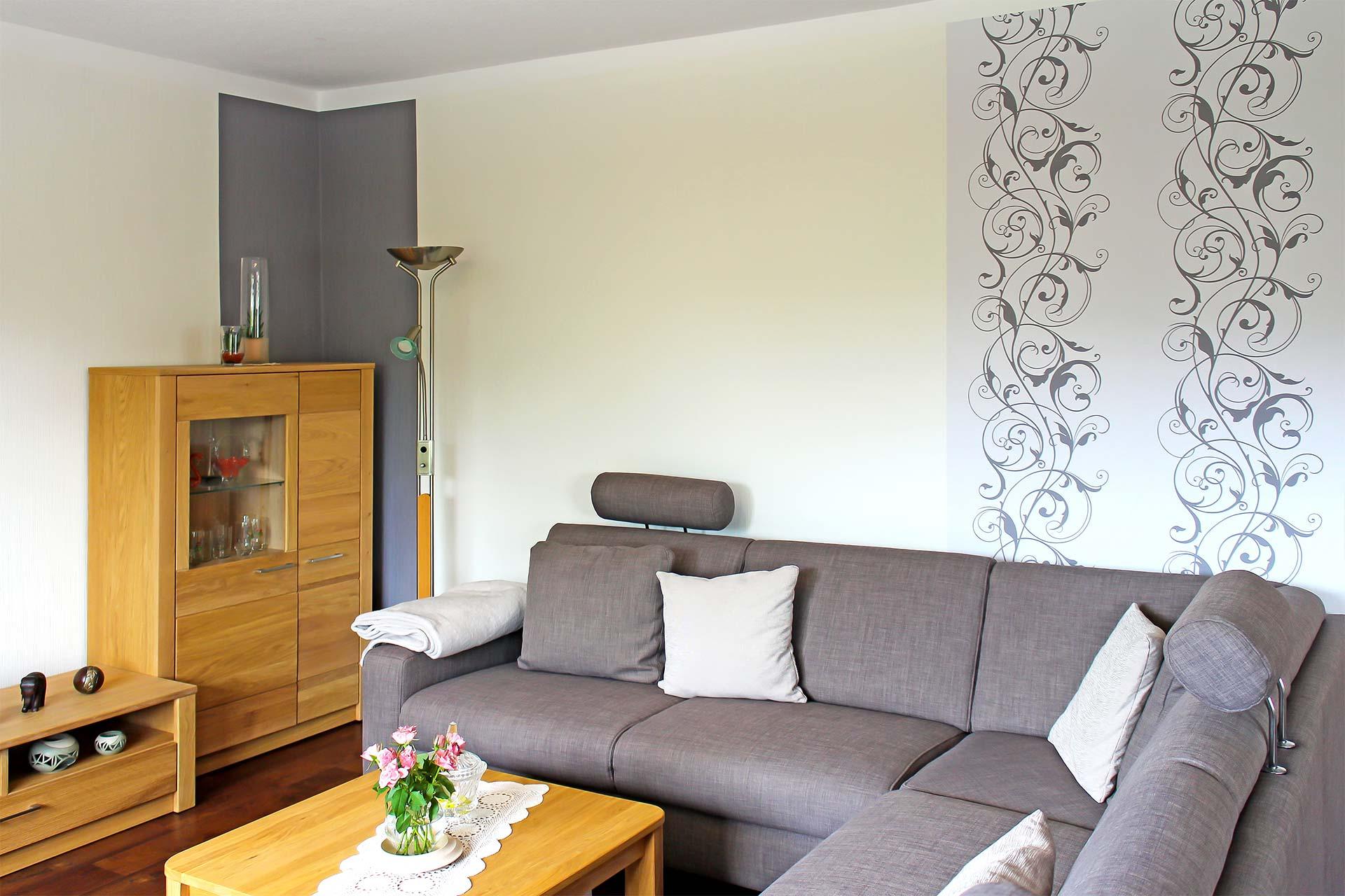 Champagnerfarbene Wand mit grauen Streifenelementen sowie dekorativem Muster