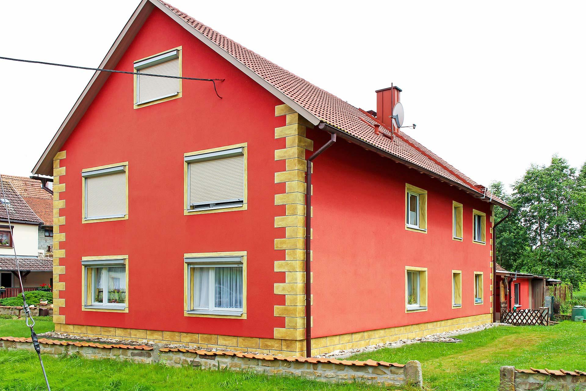 Außenfassade eines Wohnhauses mit auffälligem roten Außenputz und immitierten Sandsteinen mit Lasur