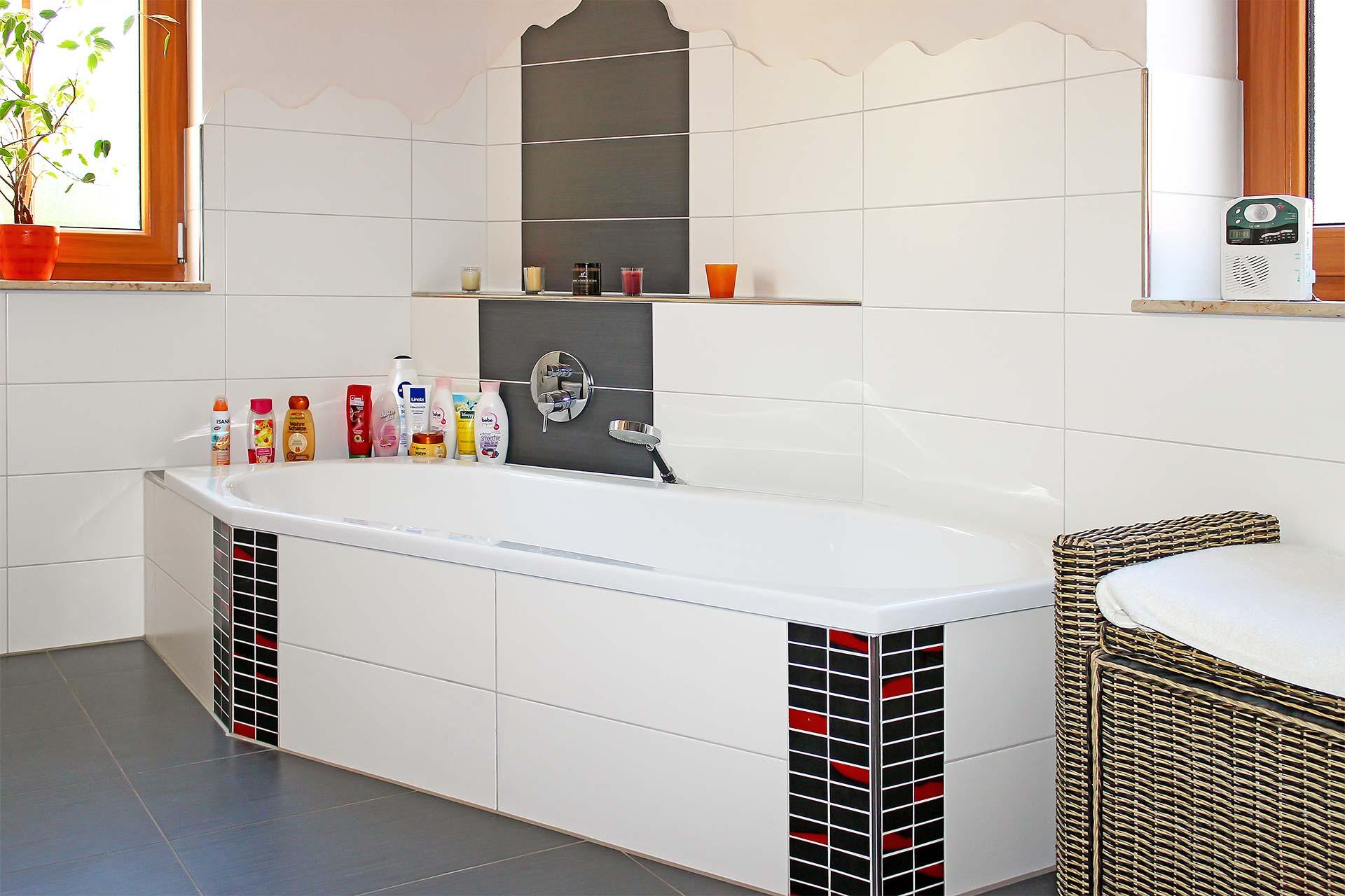 Badezimmer und Badewanne mit großformatigen Fliesen und Mosaikverzierungen
