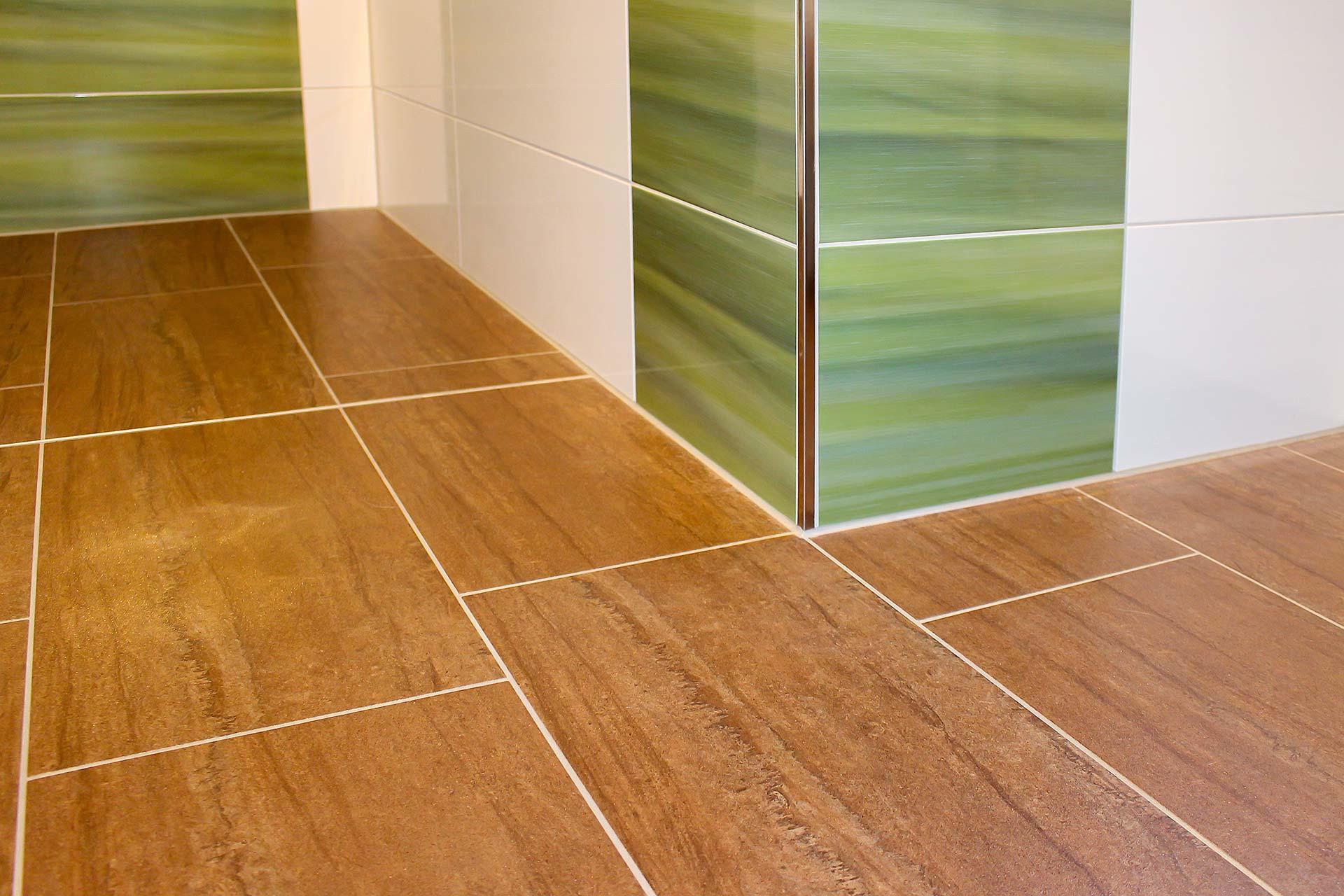 Badezimmer mit weißen und grünen Wandfliesen sowie braunen Bodenfliesen