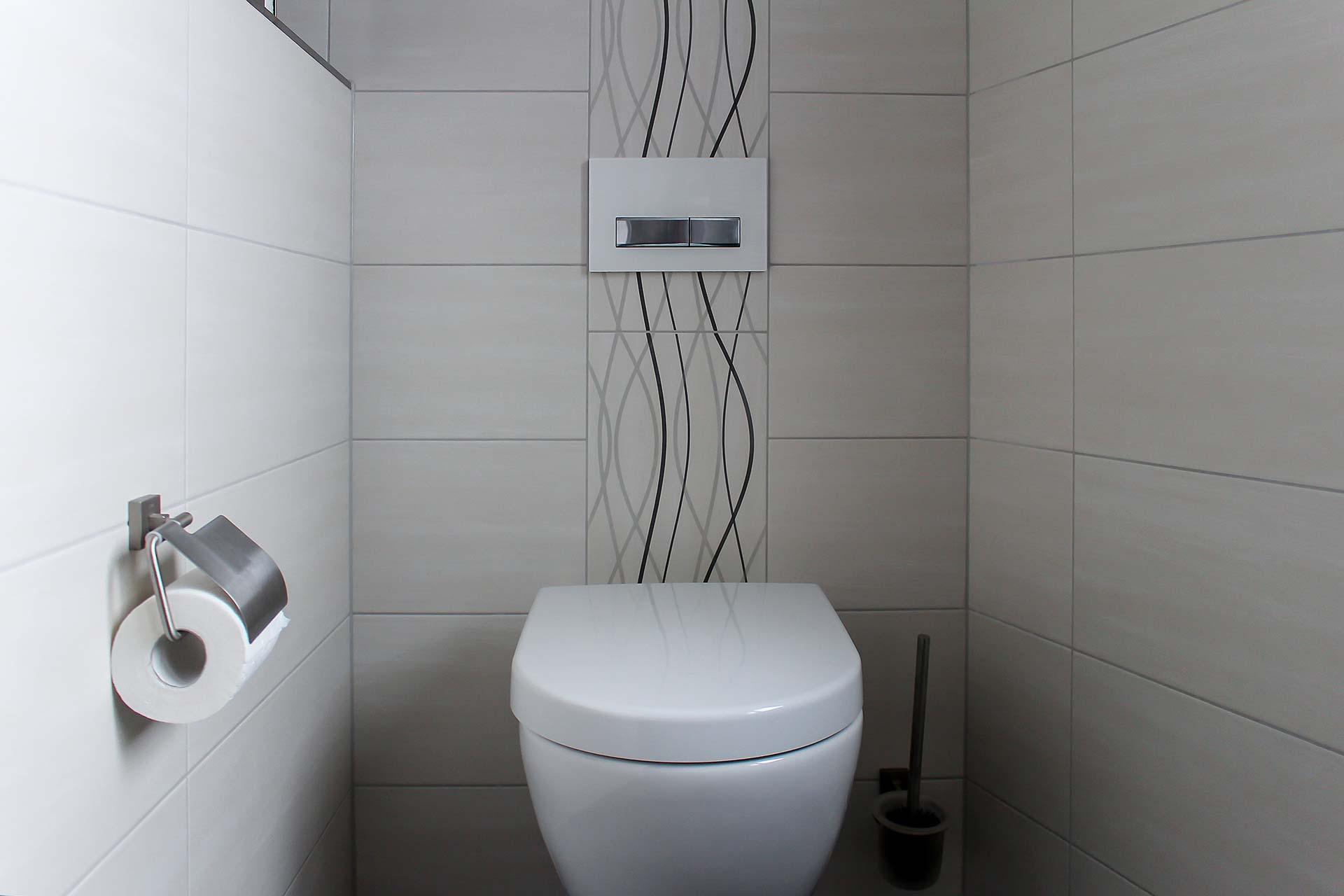 Gäste-WC mit Fliesen, teils mit dekorativem Muster