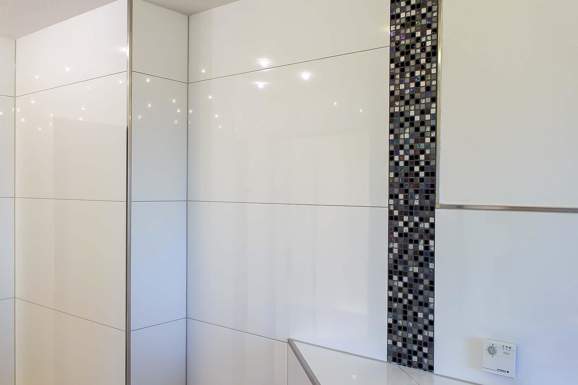 Badezimmer mit großformatigen Wandfliesen und Mosaikeinsätzen